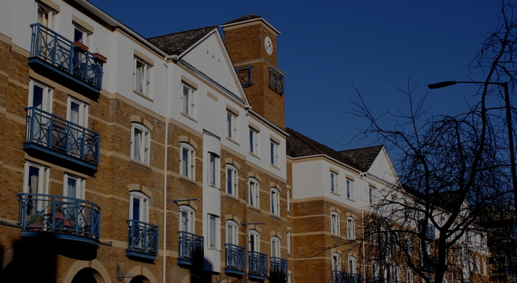 The windows and balconies of flats facing the street, above which sits the clock tower and pointed roofs of the development.