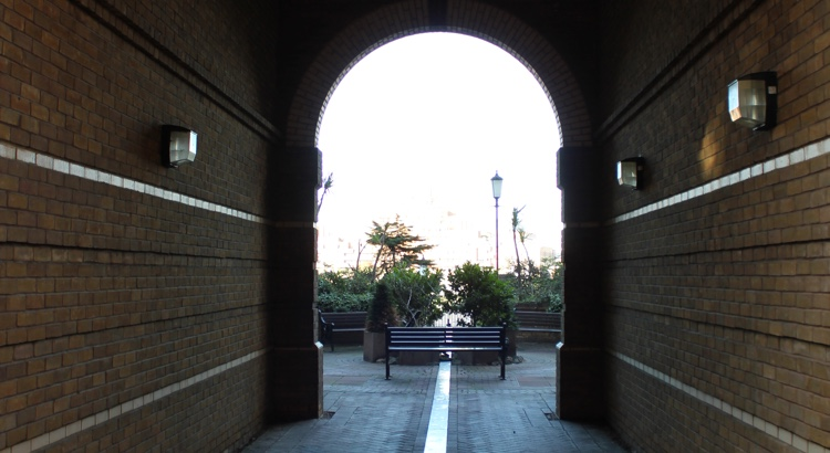 Seating area with benches and plants, viewed through an archway